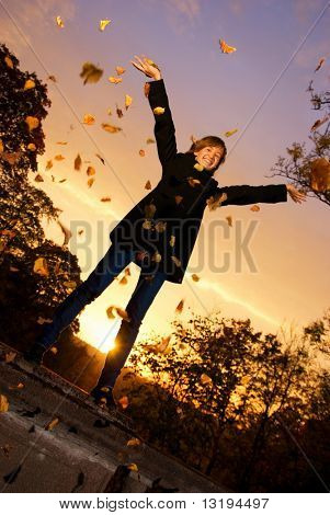 Young girl throwing autumn leaves at sunset time