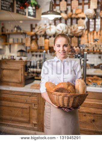 Smiling woman with basket of bread