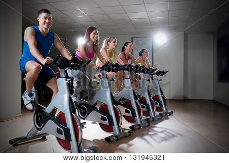 Smiling people on bikes indoors