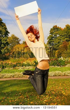 Beautiful redhead girl jumping with a white noticeboard on autumn background