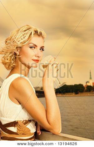 Schönes blondes Mädchen trinkt Champagner nahe dem Fluss bei Sonnenuntergang