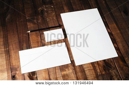 Blank stationery set on vintage wooden table background. Photo of blank letterhead business cards envelope and pencil.