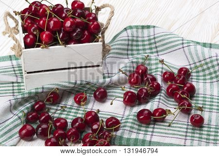 red cherries in a wooden box on wooden desk
