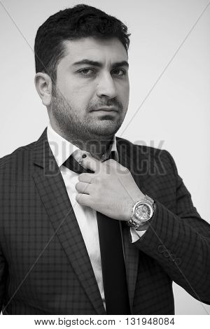 Man fixing his tie. Professional businessman in a white background. Black and white photo