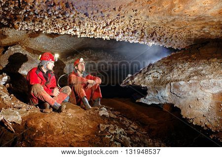 Two Spelunkers Resting In A Cave