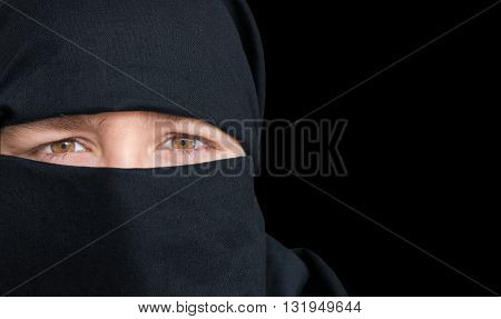 Eyes Of Young Woman In Black Niqab Scarf. Isolated On Black Back