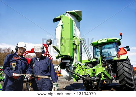 two mechanics, farmers with tractors and mowers in background, latest models of farming machinery