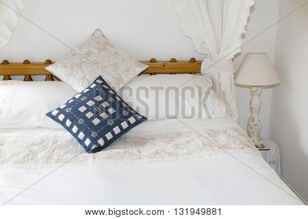 Four poster bed made up with classical style white linen and pillows with decorative cushions