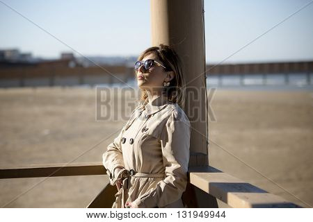 portrait of middle-aged depressed woman on balcony over sea. beautiful young woman enjoying the freshness of the morning on the balcony