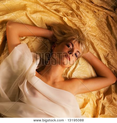 Portrait of a lovely beautiful blond girl lying in a bed