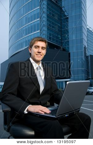 Business man sitting in front of the office building and working on his laptop