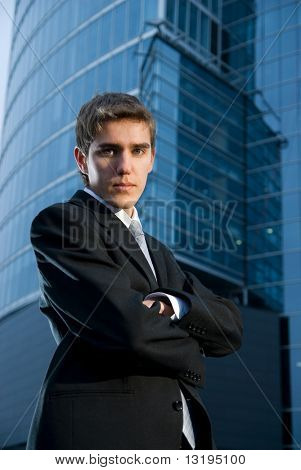 Young confident business man posing in front of office building