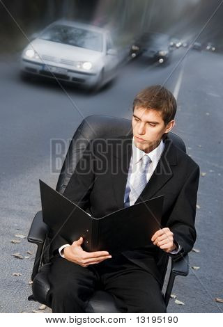 Handsome business man on sitting in executive chair on a road
