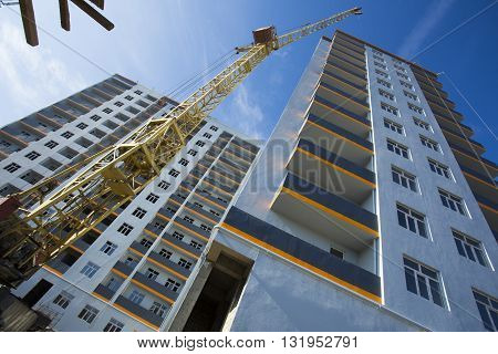 crane against sky building a new block of flats. new multi-storey house. Building crane and building under construction against cloudy sky.