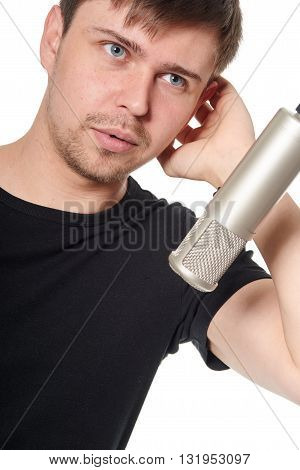 Portrait of handsome young man singing into studio microphone on white background