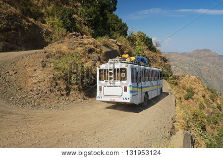 AXUM, ETHIOPIA - JANUARY 23, 2010: Tourist bus pass by the narrow gravel mountain road in Axum, Ethiopia.