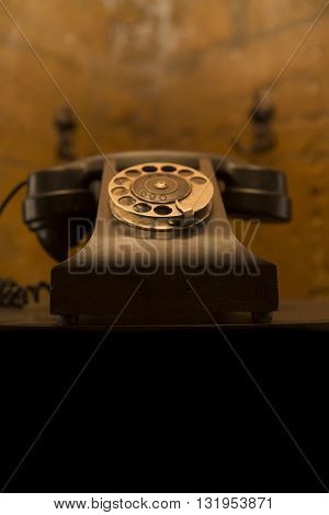 an old telephon with rotary dial. Old-fashioned phone on vintage background. Retro black old phone on the table. antique
