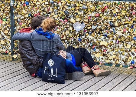 PARIS, FRANCE - MAY 14, 2013: Unknown young couple are looking at a lot of