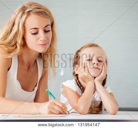 Parent helps the child to do homework. Sad girl. Mother learning her daughter