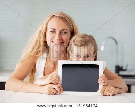 Female and child with a tablet. Family showing screen. Happy mother with girl at home