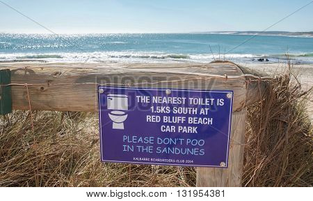 KALBARRI,WA,AUSTRALIA-APRIL 20,2016: Funny and misspelled beach sign at the dune entrance to Jake's Point with the Indian Ocean waters, dune vegetation and a blue sky in Kalbarri, Western Australia.