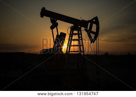 Fossil Fuel Energy, Oil Pump, Pumpjack, Old Pumping Unit, Jack Pump, Sunset.Rows of oil donkey in silhouette at sunset crude oil.