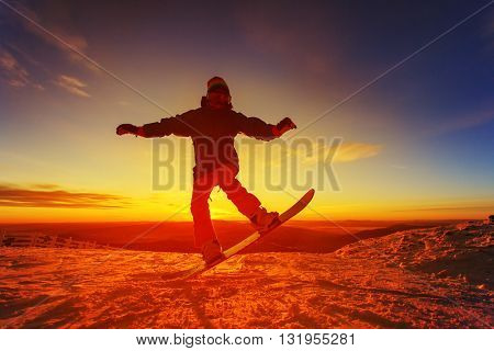 Snowboarder on the mountain with a sunset in the background