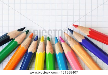 white squared paper notebook with colored pencils