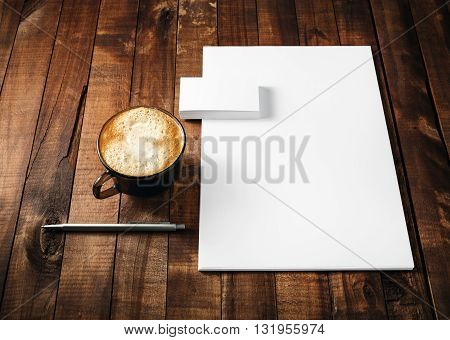 Blank paperwork and corporate identity template on vintage wooden table background. Blank letterhead business cards coffee cup and pen. Mock-up for ID. Blank stationery template for design portfolios.
