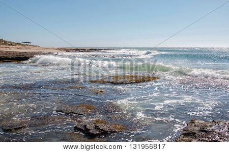 Coral coast seascape with natural rock formations, Indian Ocean seascape and waves crashing the beach at Jake's Point under a clear blue sky in Kalbarri, Western Australia.