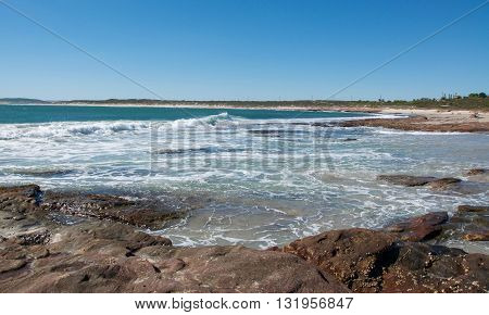 Jake's Point beach with turquoise Indian Ocean waves and beach reef under a clear blue sky in Kalbarri, Western Australia.