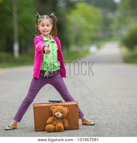 Little girl in bright clothes standing on the road with a suitcase and a Teddy bear.