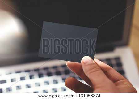 Closeup Photo Man Showing Blank Black Business Card and Using Modern Laptop Blurred Background. Mockup Ready for Private Information. Sunlight Reflections Surface Gadget. Horizontal mock up
