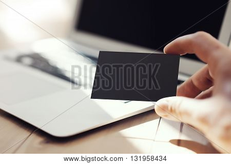 Closeup Photo Man Showing Blank Black Business Card and Using Modern Laptop Wood Table. Blurred Background. Mockup Ready for Private Information. Sunlight Reflections Surface Gadget.Horizontal mock up