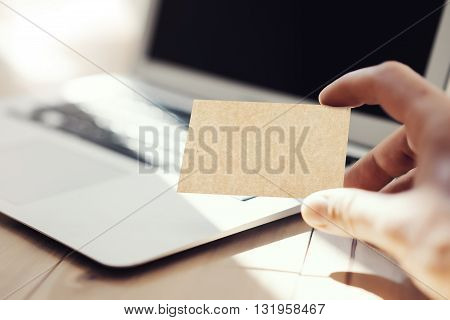 Closeup Photo Man Showing Blank Craft Business Card and Using Modern Laptop Wood Table. Blurred Background. Mockup Ready for Private Information. Sunlight Reflections Surface Gadget.Horizontal mock up