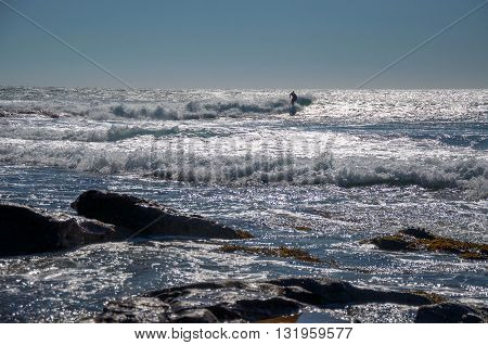 KALBARRI,WA,AUSTRALIA-APRIL 20,2016: Surfer in the glistening turquoise waves of the Indian Ocean with rocks at Jake's Point in Kalbarri, Western Australia.