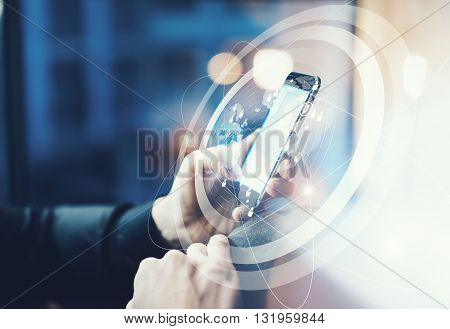 Picture businessman relaxing modern loft office. Man sitting in chair at night.Using contemporary smartphone. Digital Connections World Wide Interfaces Screen.Horizontal, film effect, blurred background