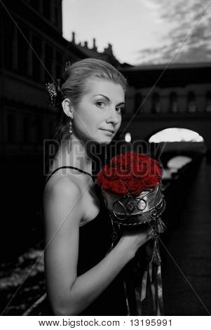 Black and white picture of a beautiful girl with roses  in old city