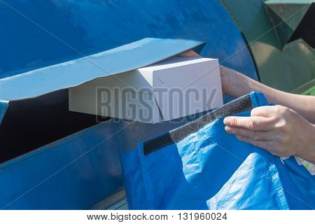 The woman is throwing a paper box from blue portable bag to blue container for sorting paper household waste.