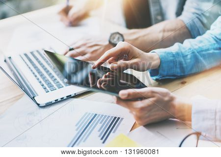 Coworkers team brainstorm in modern office.Project Manager Researching Process, Touching Screen Digital Tablet.Young Business Crew Working with Startup Studio.Graphics, reports wood Table.Closeup Photo