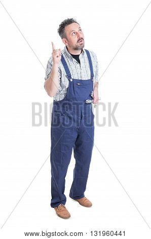 Doubtful Young Mechanic Showing Something By Pointing Finger Up