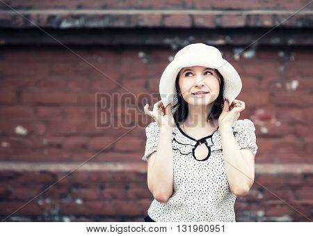 Pretty young smiling woman in a white blouse and hat posing on old vintage brick wall background. Girl holds the edges of the hat by hand. Toned photo with copy space. Vintage style photo.