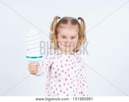Little Girl Shows A Large Energy-saving Light Bulbs.