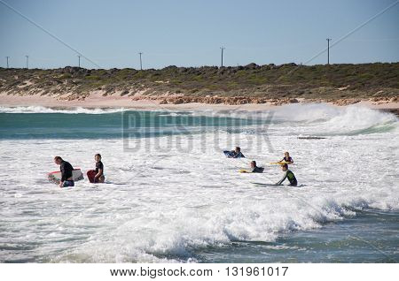 KALBARRI,WA,AUSTRALIA-APRIL 20, 2016: Tourists body boarding in the turquoise Indian Ocean waters at the tourist destination Jake's Point in Kalbarri, Western Australia.