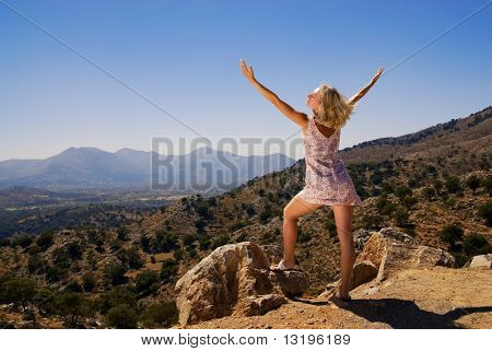 Beautiful girl standing on a mountain with her hands wide open