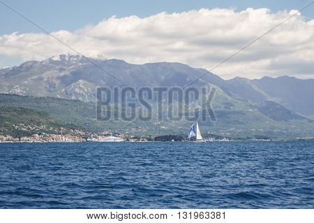 Boat sailing on the background of mountains. Regatta