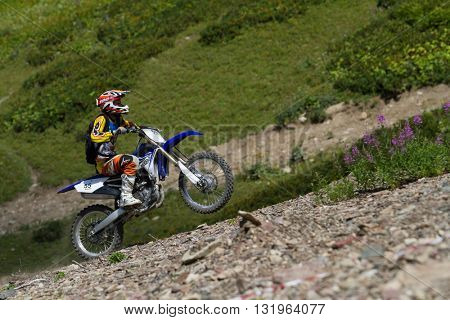 SOCHI, RUSSIA - AUGUST 16, 2014: Off-road motorcycle rider in summer mountains