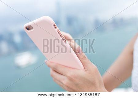 Human hand sending sms on cellphone