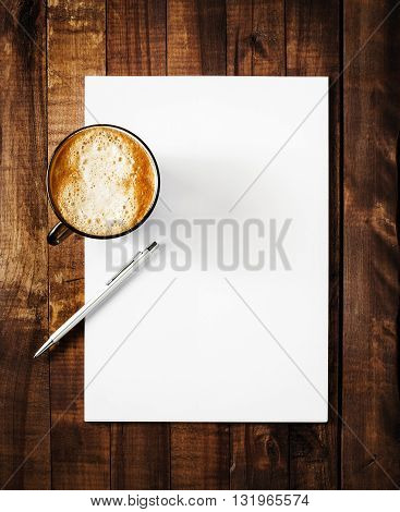 Blank paperwork mock-up. Blank letterhead with plenty of copy space coffee cup and pen. Blank template for branding identity on vintage wooden table background. Top view.
