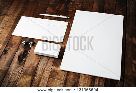 Blank stationery set on vintage wooden table background. Mock-up for branding identity. Blank template for design portfolios. Letterhead business cards envelope and pen.